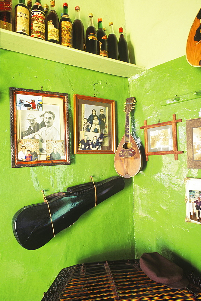 Guitar with picture frames hanging on a wall in a bar