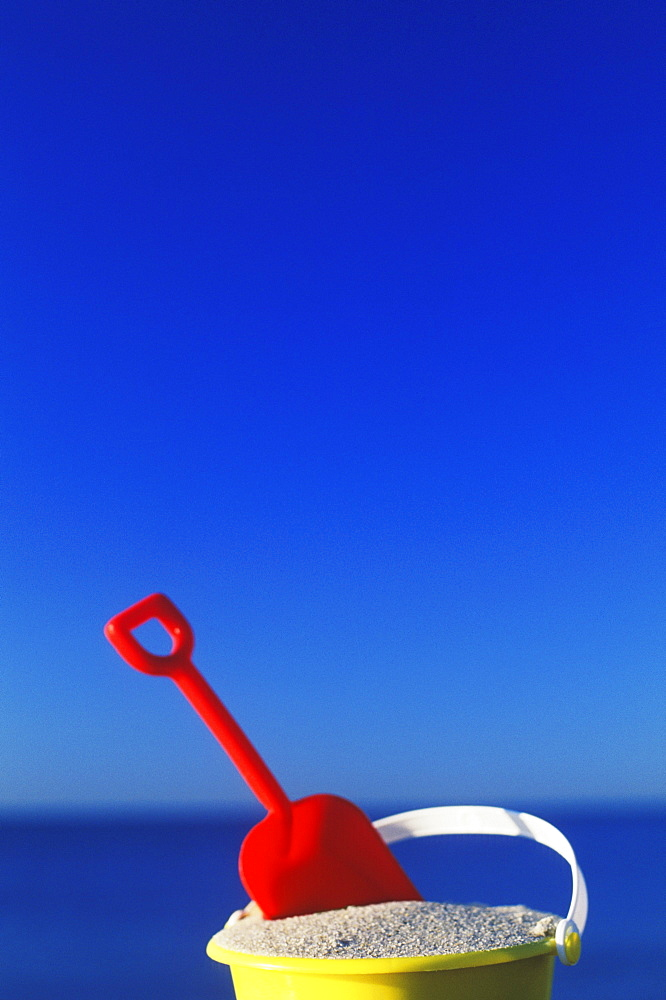 Close-up of a shovel in a sand pail