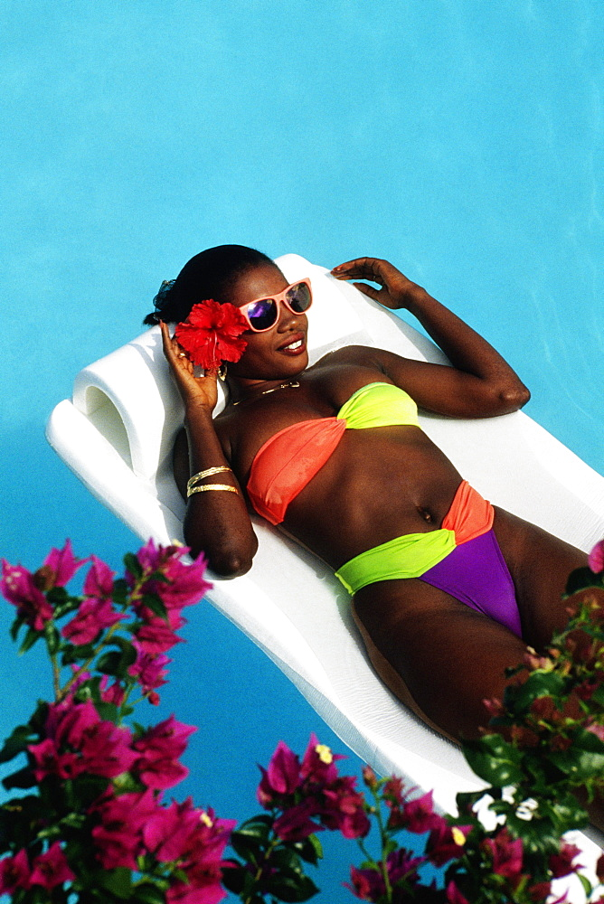 An African-American woman is floating on an inflatable mattress in a swimming pool, Destiny Villa, Jamaica