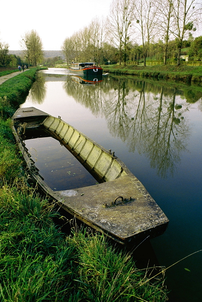 High angle of an old boat with a barge moving upstream, Burgundy Canal, France