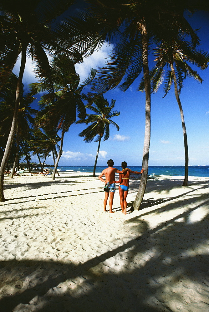 A couple on a holiday on a white sandy beach, Barbados