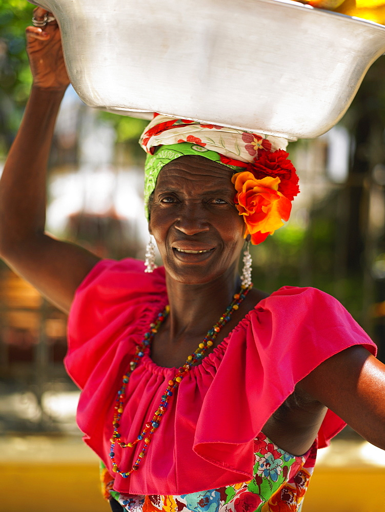 Portrait of a market vendor carrying a basket on her head, Cartagena, Colombia