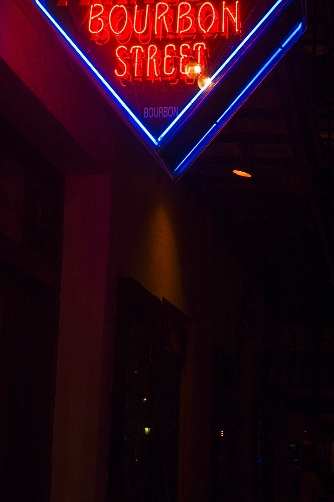 Low angle view of a street name sign lit up at night, New Orleans, Louisiana, USA