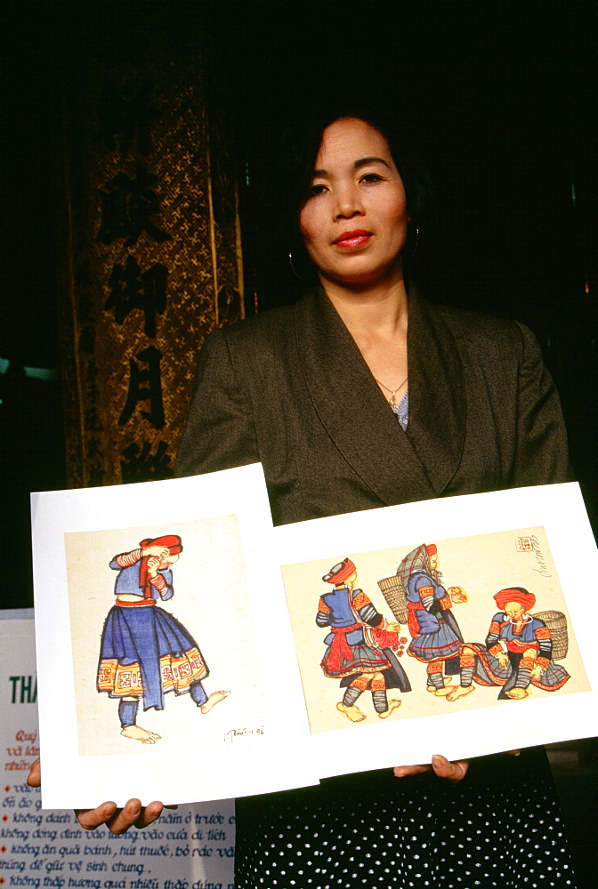 Portrait of a young woman showing paintings