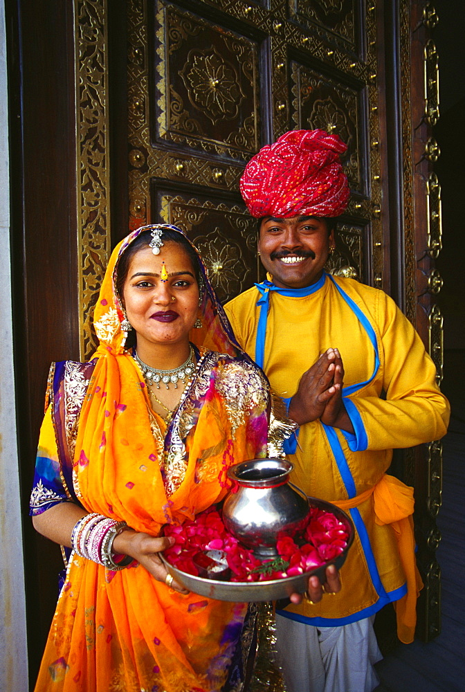 Portrait of a mid adult couple at a door and greeting, Jaipur, Rajasthan, India