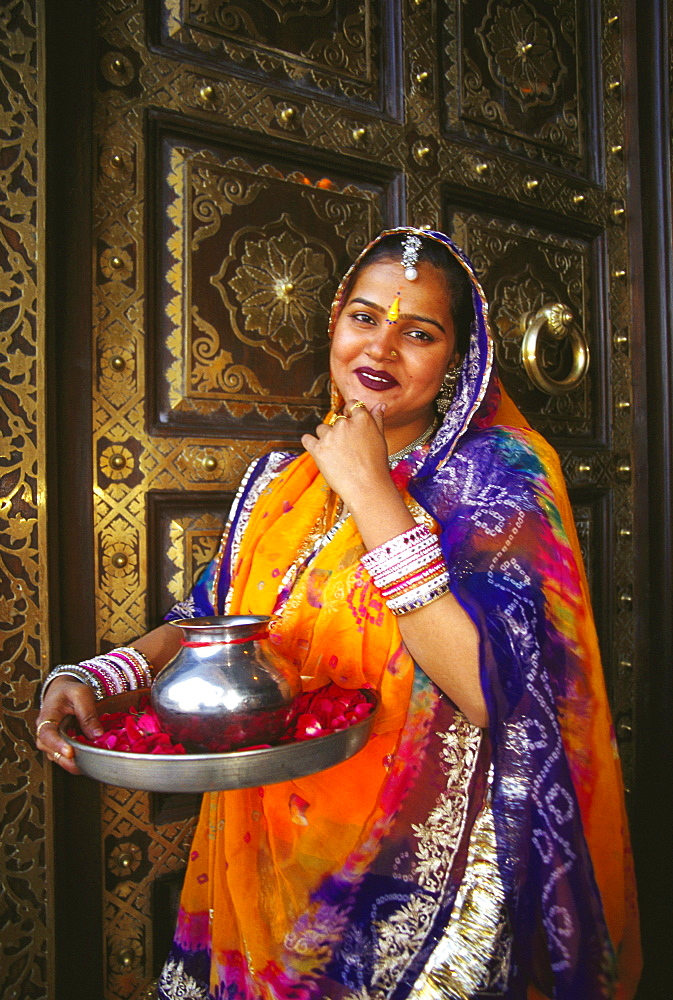 Portrait of a mid adult woman standing in front of a door and greeting, Jaipur, Rajasthan, India