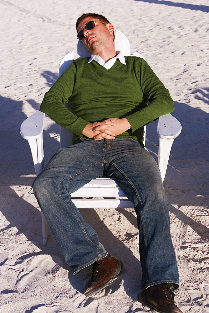 High angle view of a mid adult man reclining on a lounge chair