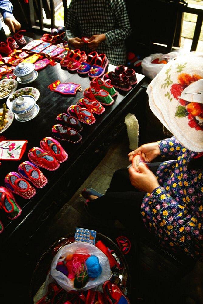 High angle view of three women sewing baby booties, Zhouzhuang, Kunshan City, Jiangsu Province, China