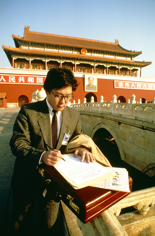 Businessman standing in front of a palace and writing with a pen on a sheet of paper, Tiananmen Gate Of Heavenly Peace, Tiananmen Square, Beijing, China