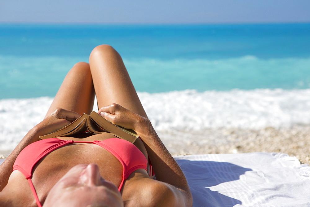 woman, holding book, lying on towel on sunny beach - 786-10013