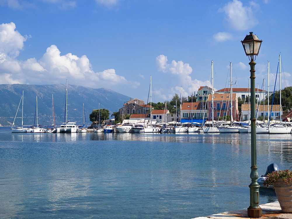 Greece, Kefalonia, Fiskardo, view of lamp and yachts in sunny coastal harbour