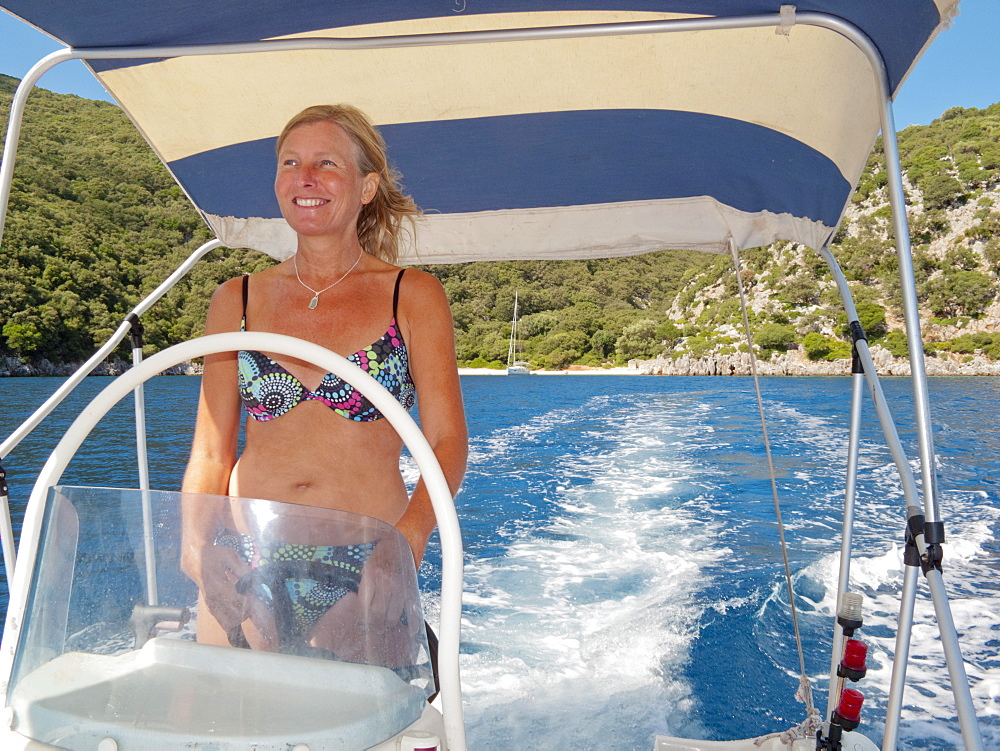 Woman steering a boat away from sunny coastline