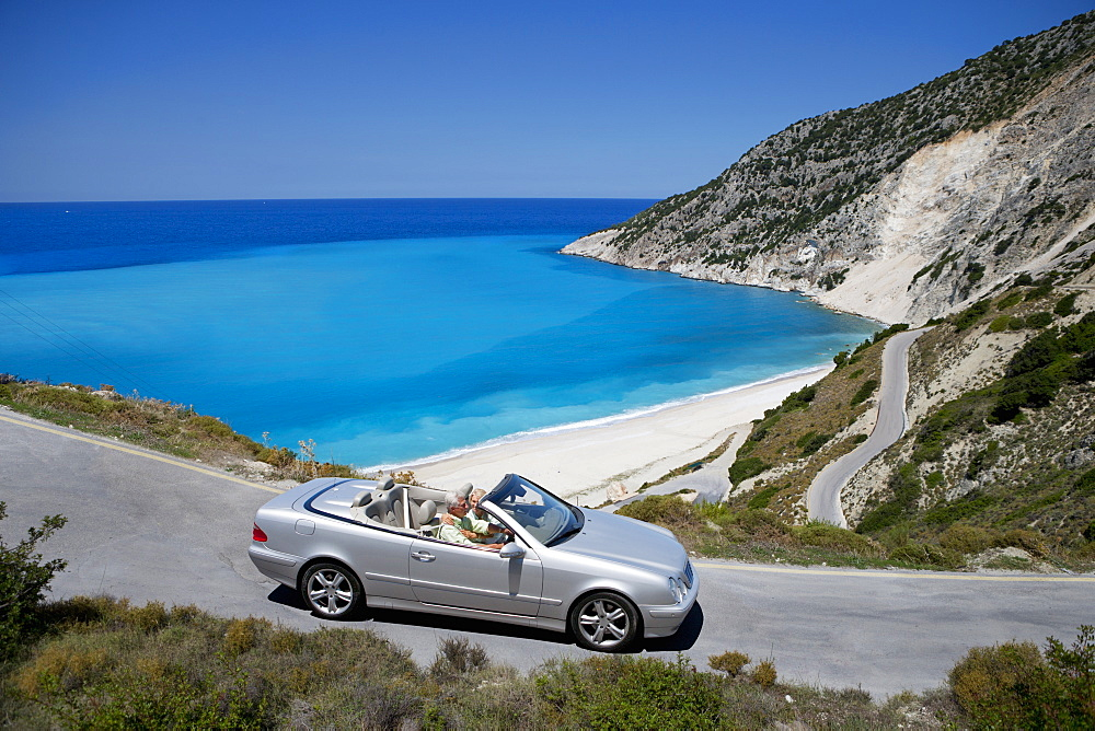 Senior couple driving convertible car along winding coastal road