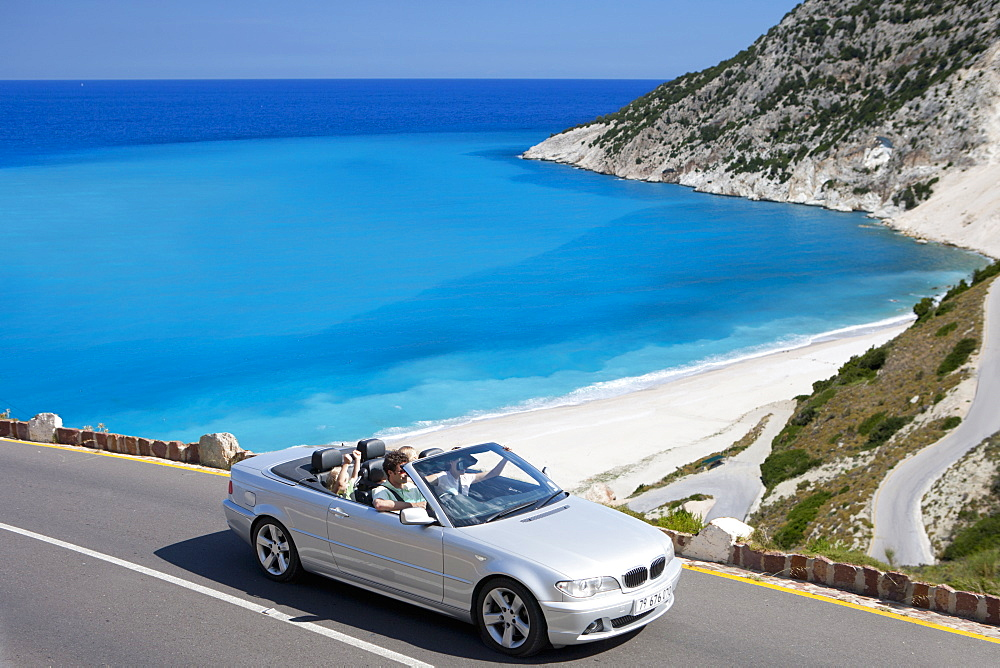 Family driving convertible car along winding coastal road - 786-10069