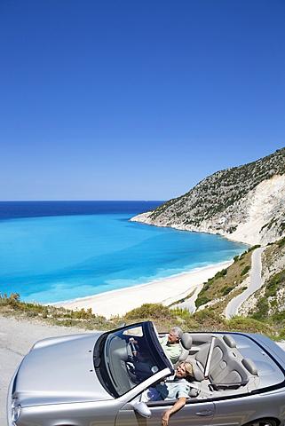 Senior couple driving convertible car along winding coastal road