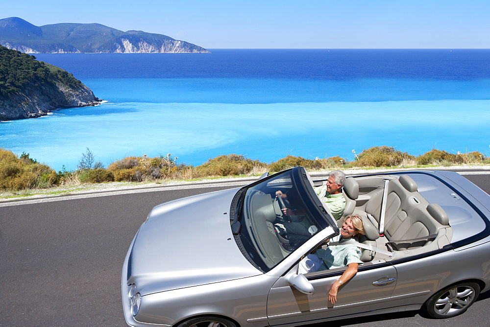 Senior couple driving convertible car along coastal road