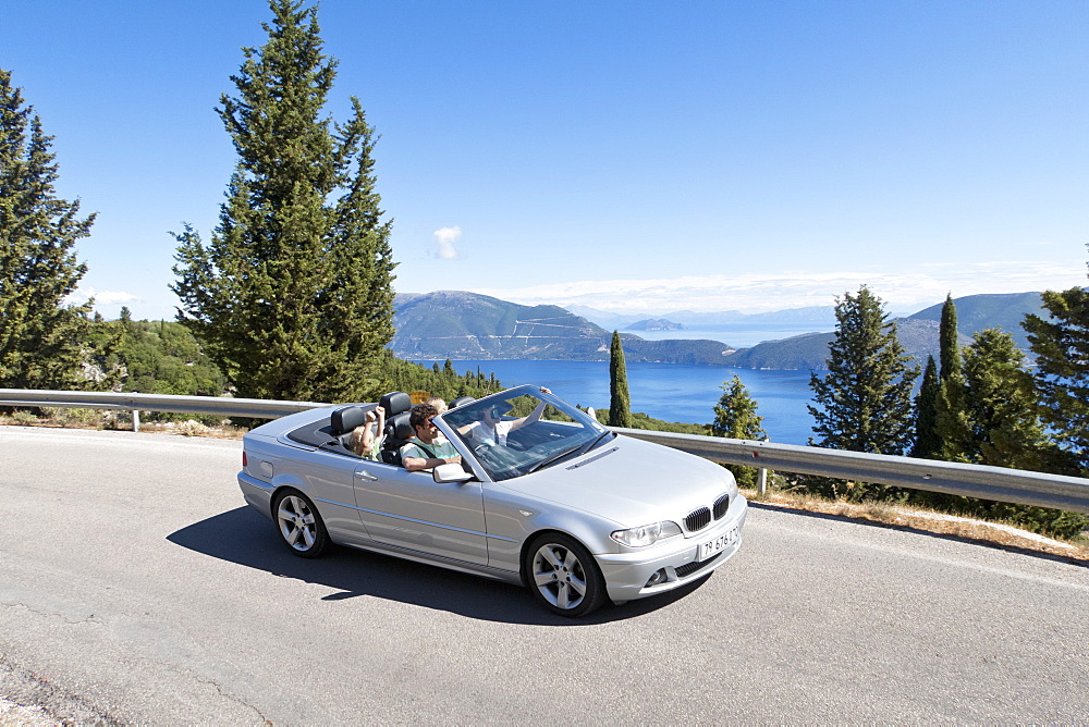 Family riding in convertible on sunny, winding road along ocean, Greece