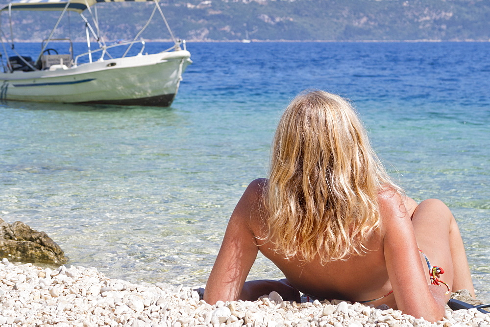 Blonde woman sunbathing on sunny beach near boat, Greece