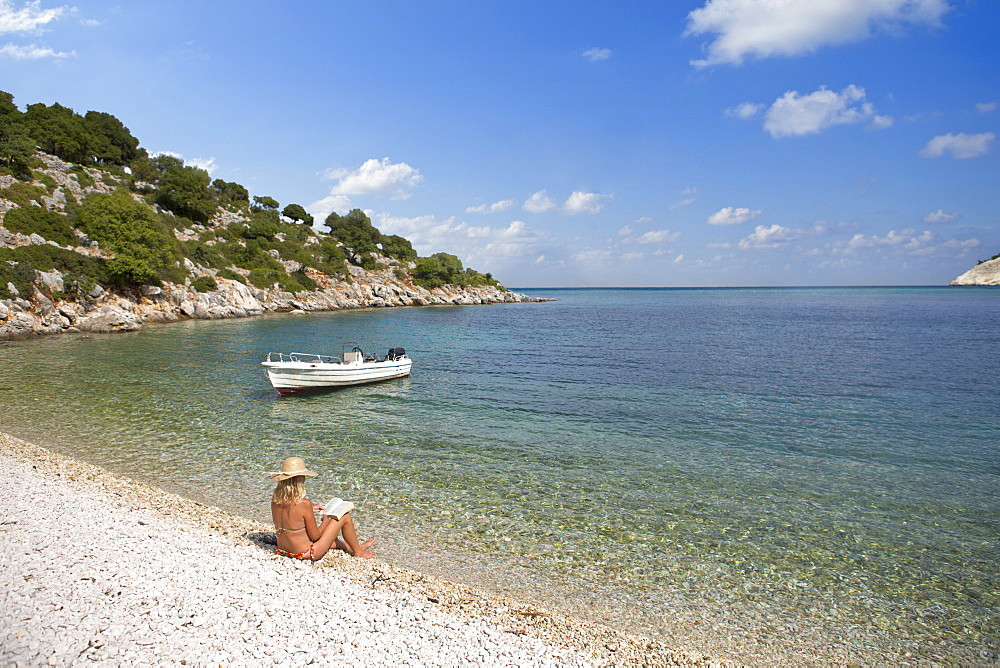 Woman in sun hat reading book on sunny beach, Greece