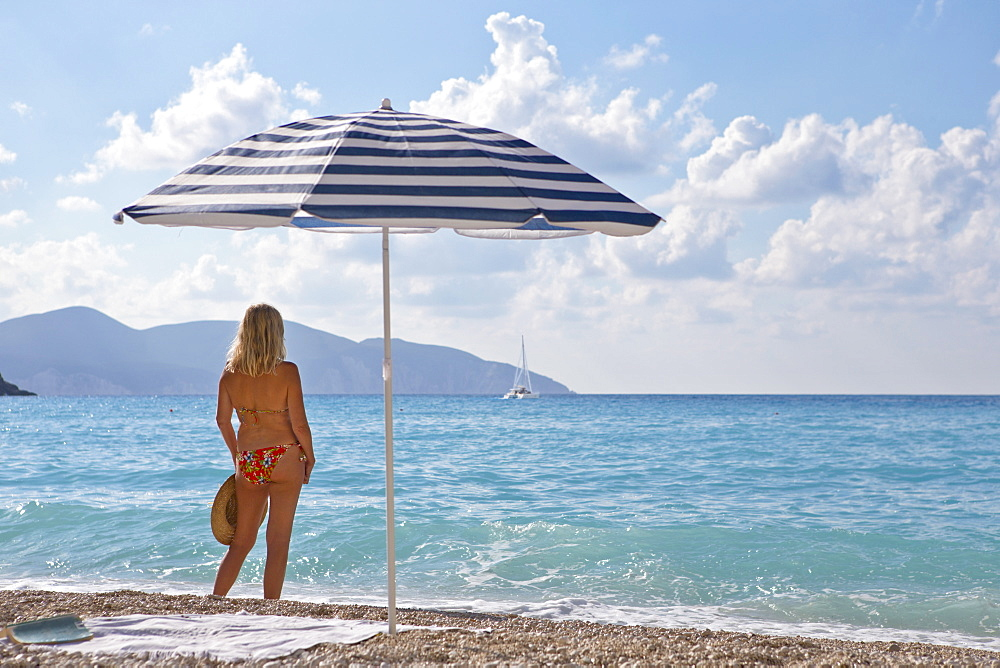 Woman standing on sunny beach looking at ocean view near beach umbrella, Greece