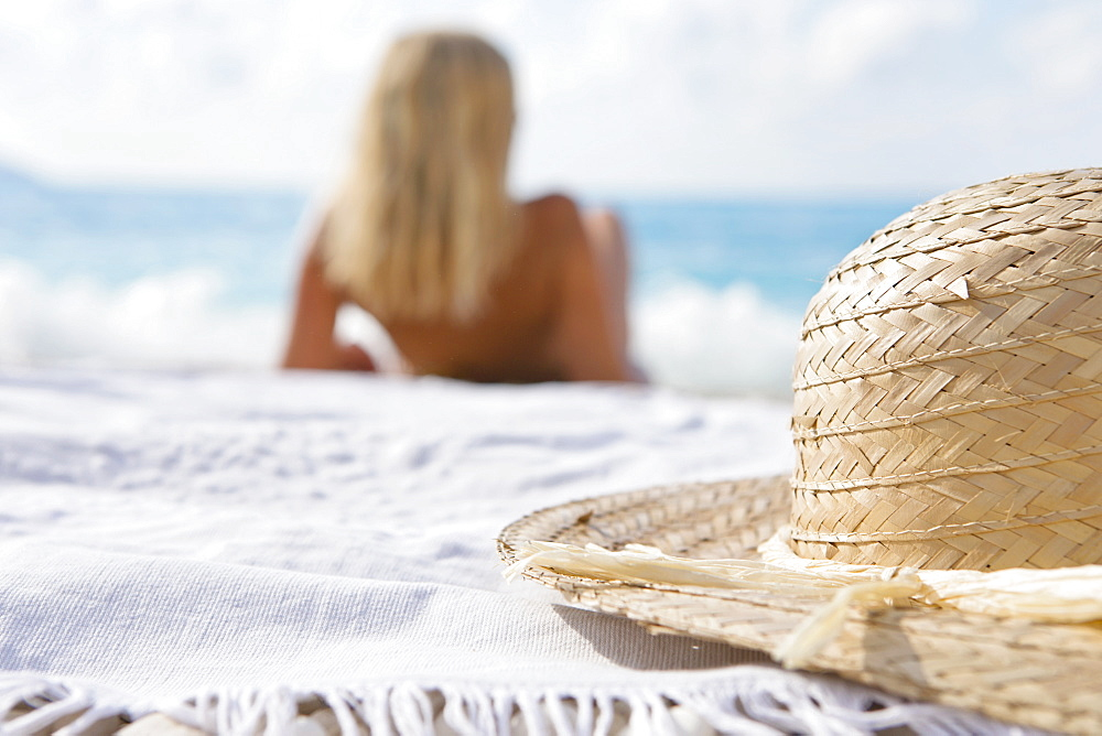 Close up of sun hat on blanket behind woman laying on beach, Greece