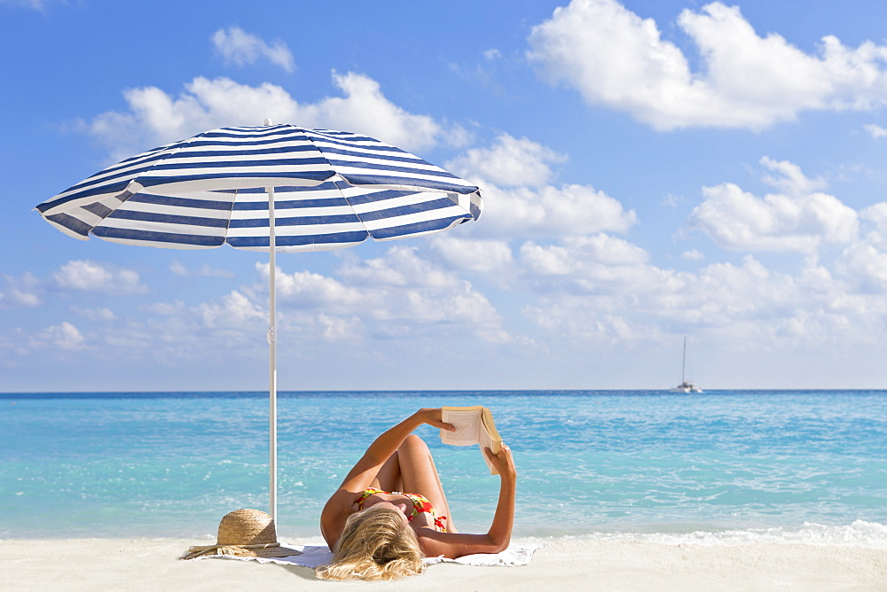 Woman laying and reading book on sunny beach under striped beach umbrella, Greece