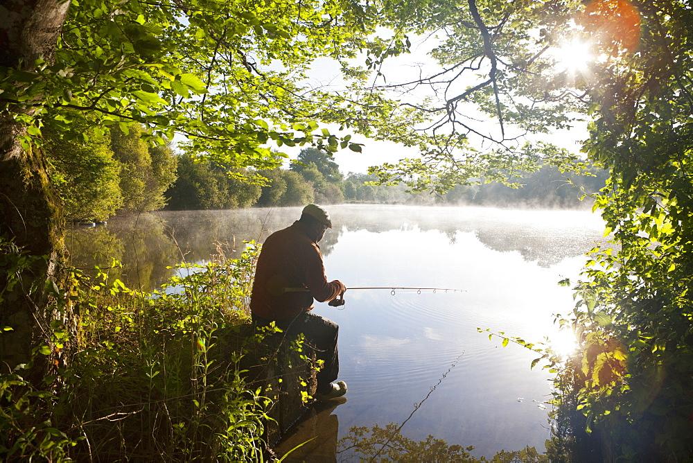 Fisherman carp fishing at tranquil lakeside among green trees