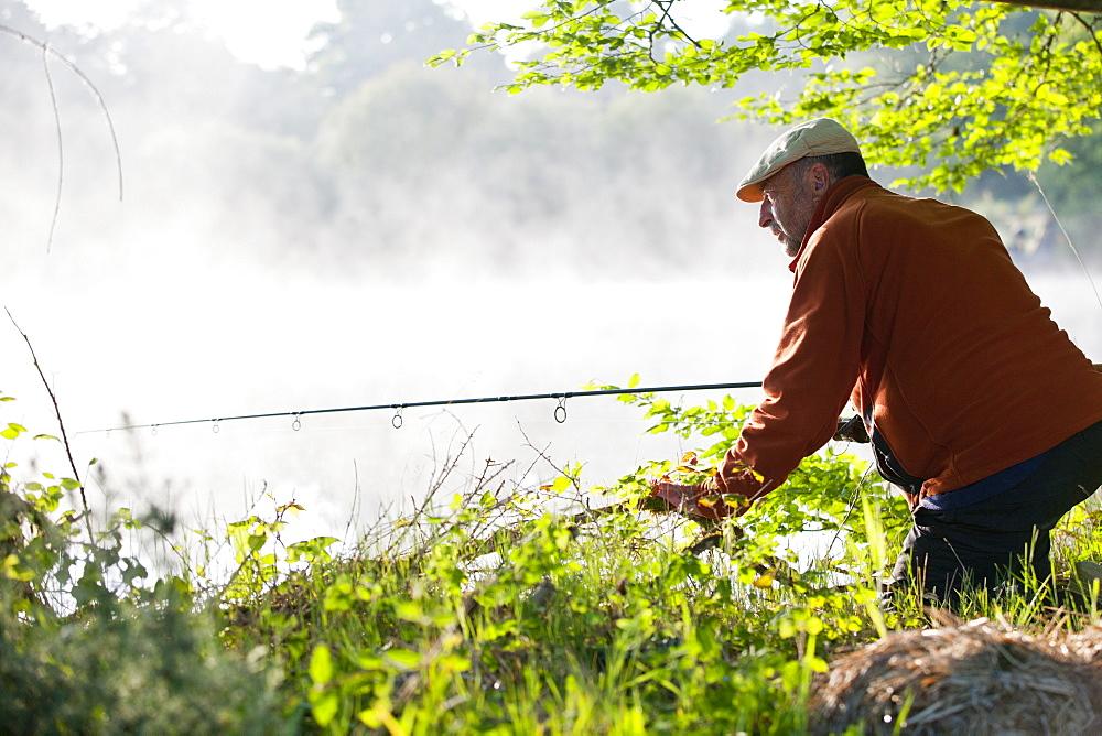 Fisherman carp fishing at misty lakeside