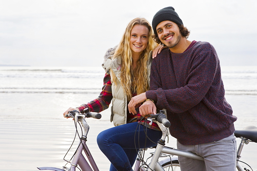 Portrait smiling couple riding bicycles on beach