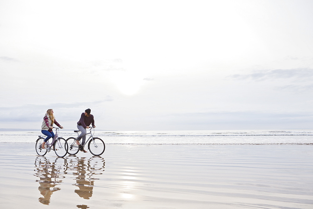 Couple riding bicycles in ocean surf - 786-10196