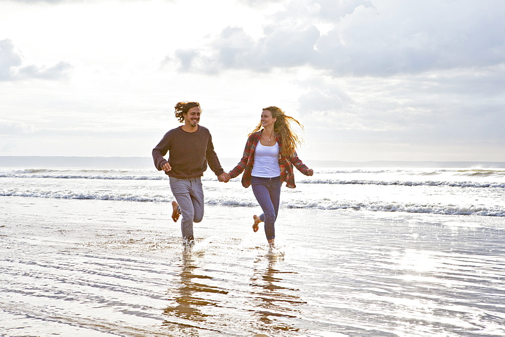 Couple running and holding hands in ocean surf