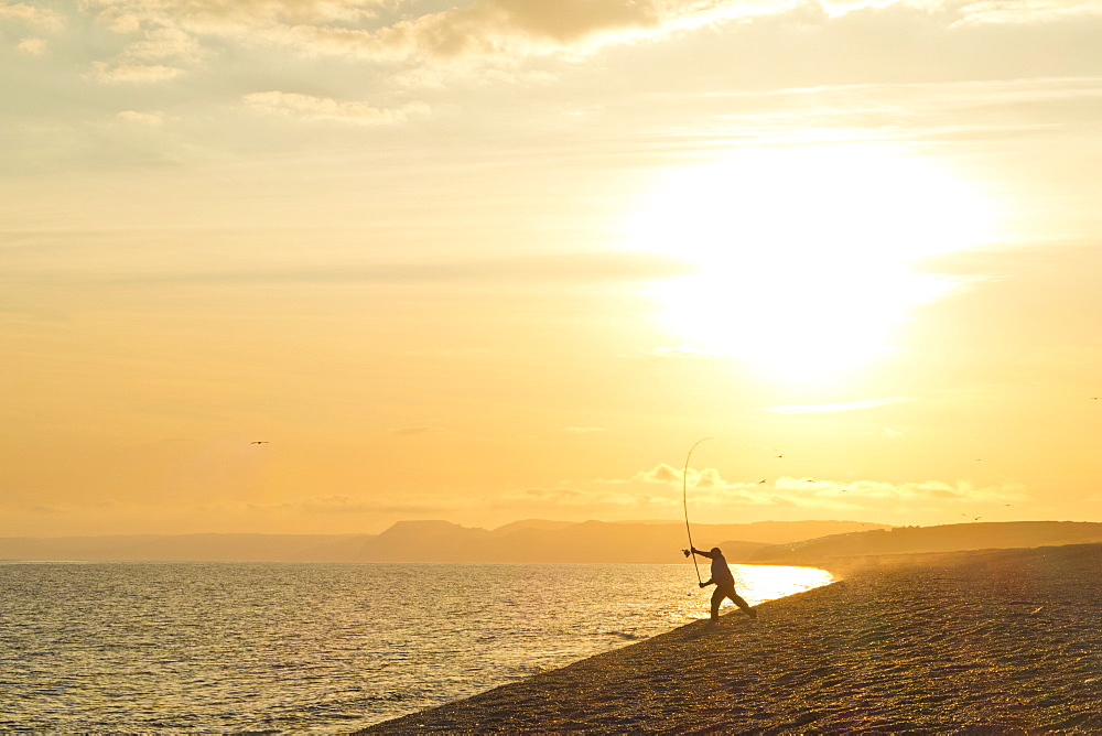 Fisherman beachcasting into ocean on tranquil beach at sunset