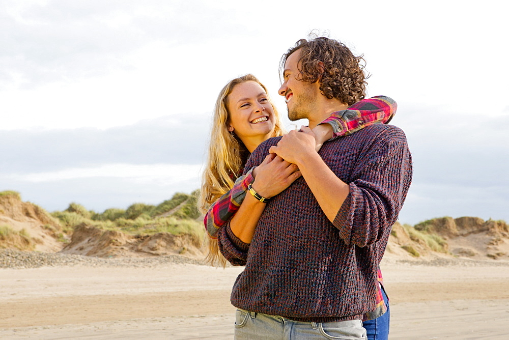 Couple hugging face to face on beach