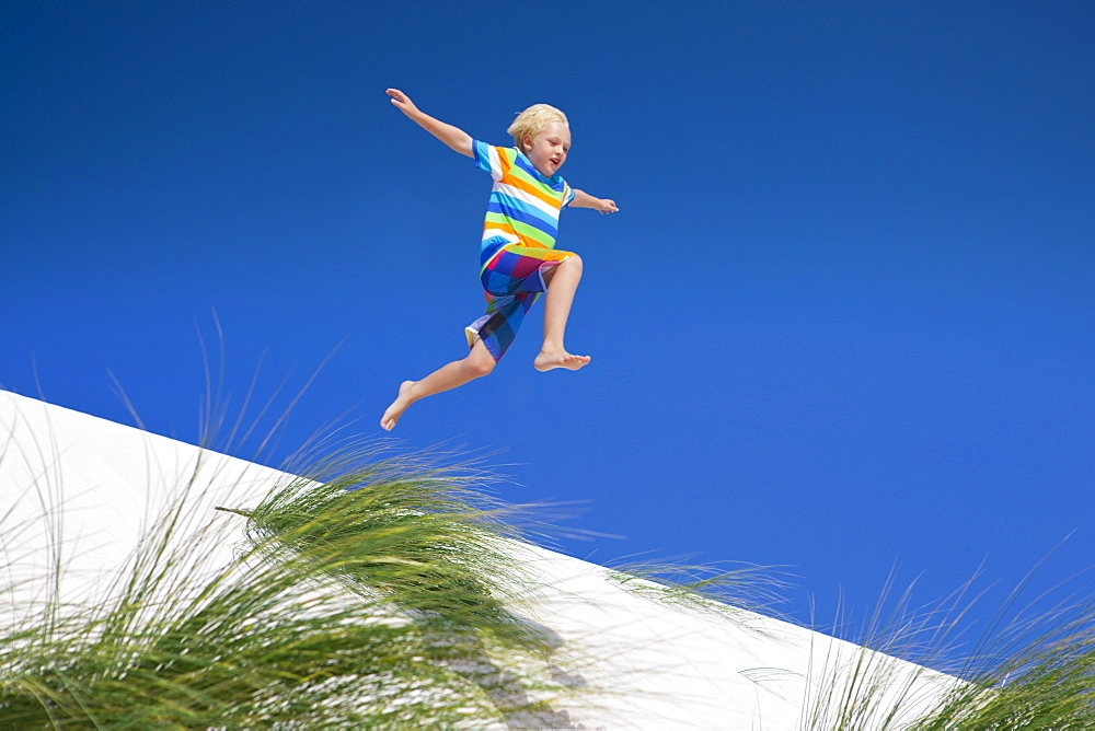 Exuberant boy jumping for joy over sand dune beach hill - 786-10205