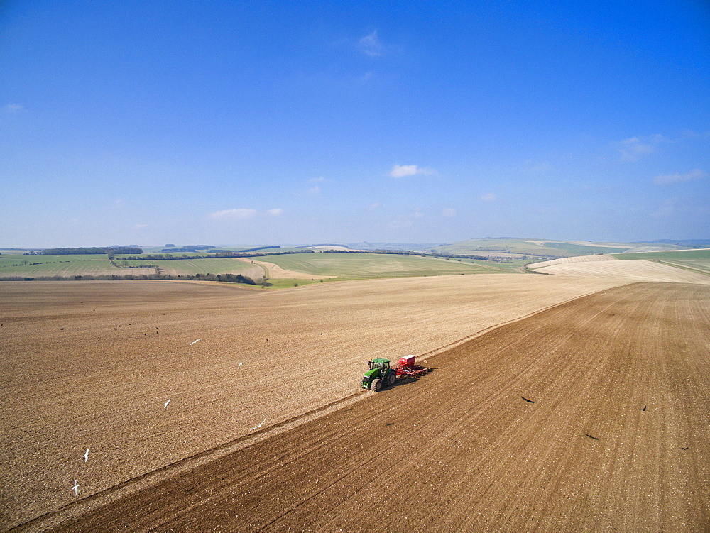 Aerial View Of Tractor Pulling Drill Sowing Seed In Field (Drone)
