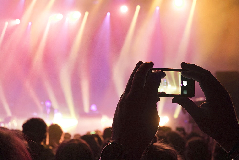 Music Fan Taking Picture On Mobile Phone At Rock Concert