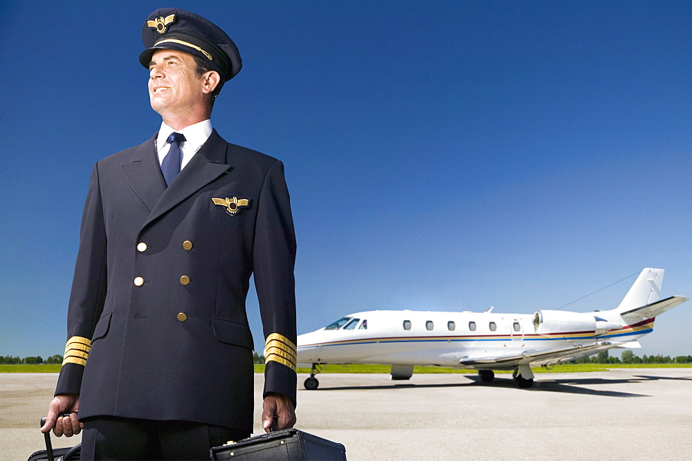 Pilot Of Private Jet Standing By Aircraft On Tarmac