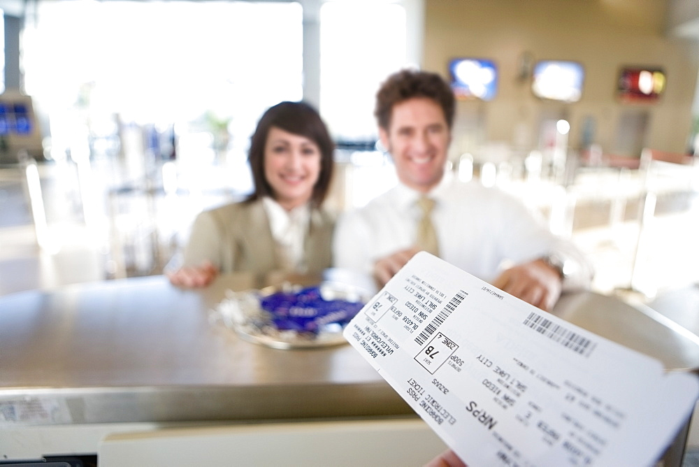 Businesspeople With Tickets At Airport Check In Desk