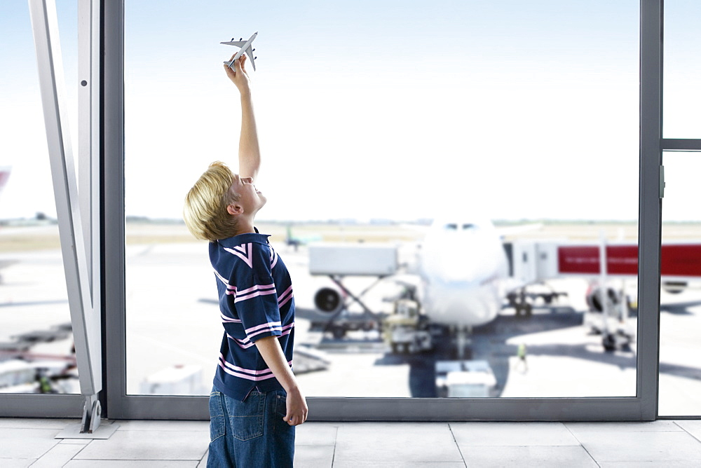 Boy Playing With Model Plane In Airport Departure Lounge