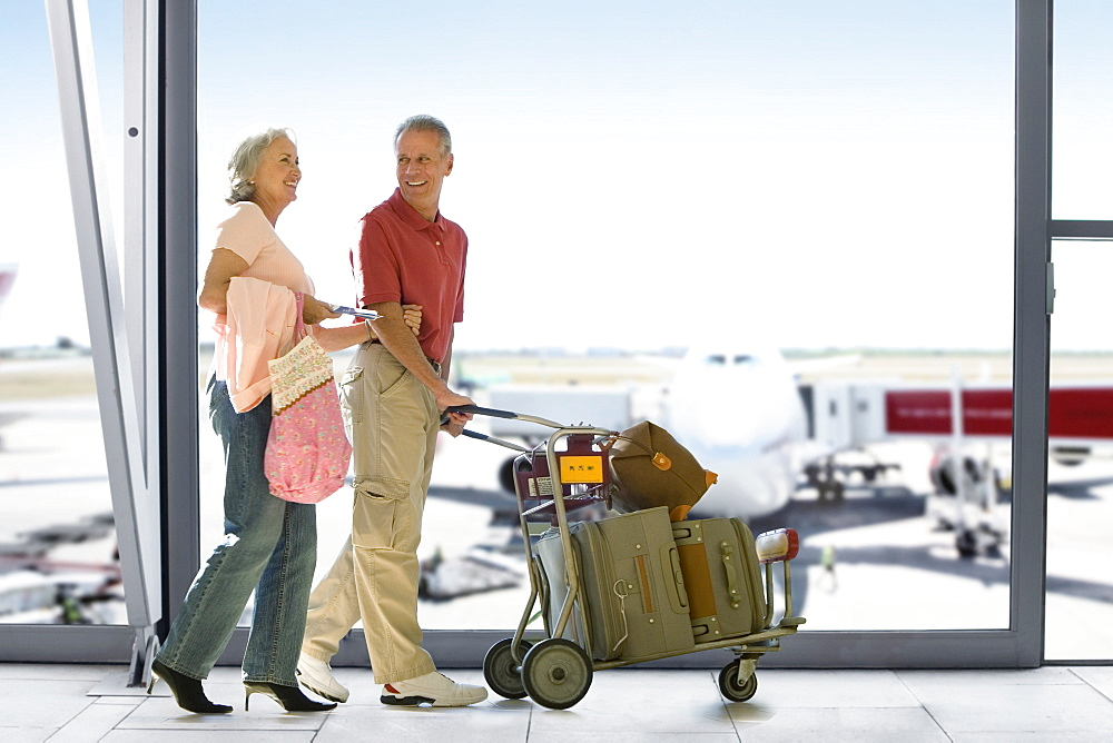 Senior Couple With Luggage In Airport Departure Lounge