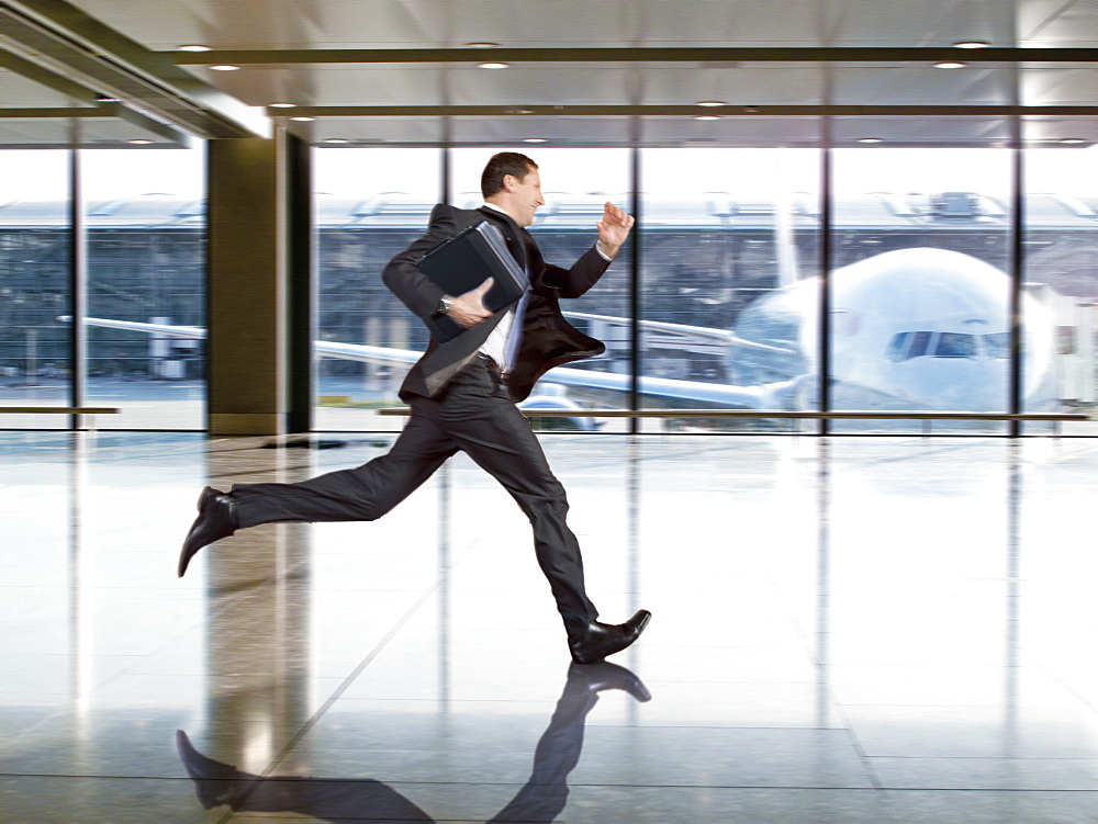 Businessman Running To Catch Flight At Airport