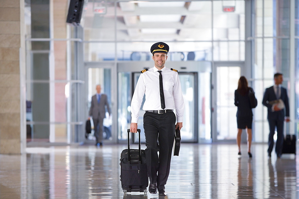 Portrait Of Airline Pilot Walking Through Airport Lounge