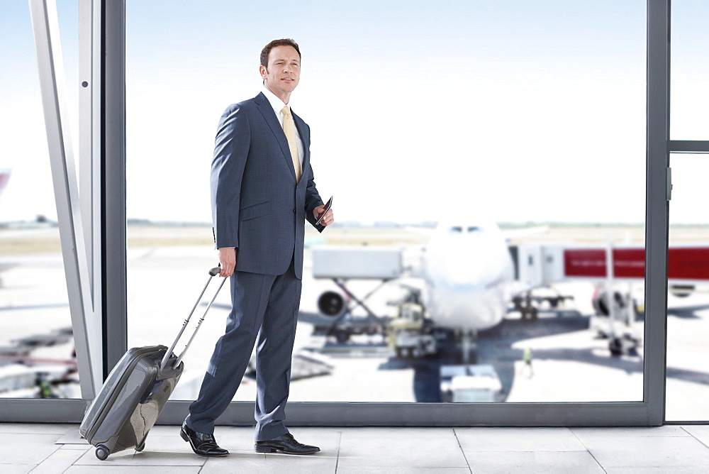 Businessman With Luggage In Airport Departure Lounge
