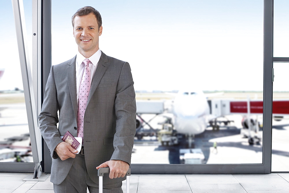Businessman At Airport With Luggage And Passport