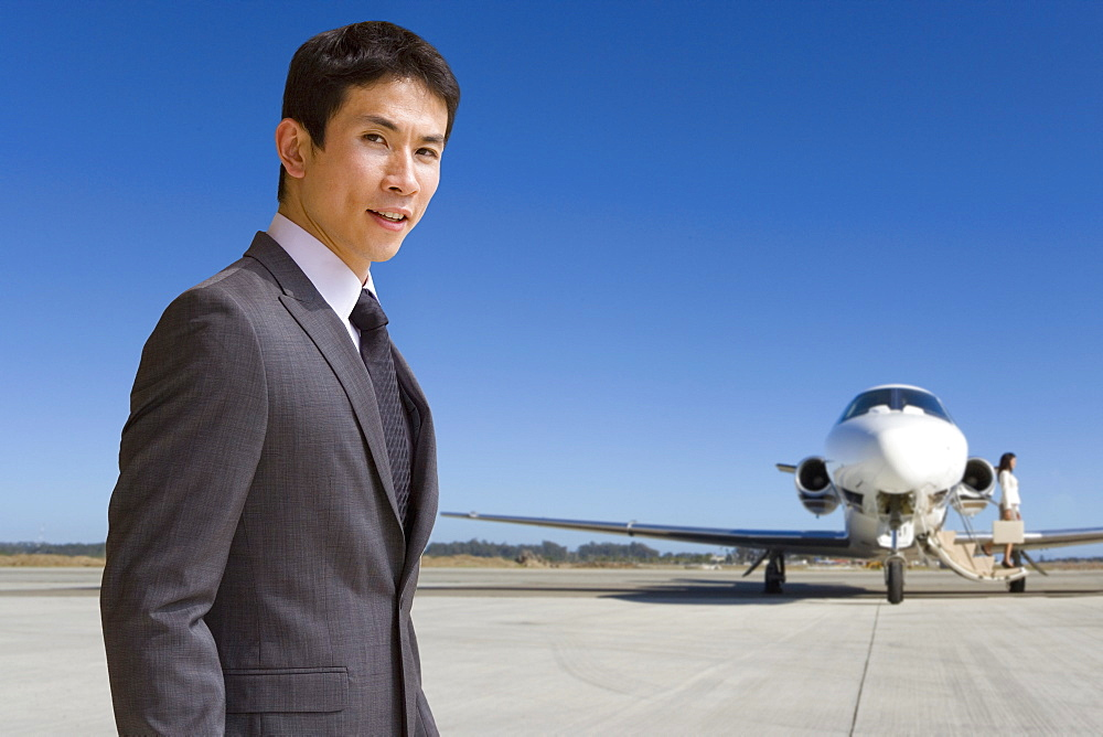Portrait Of Businessman Boarding Private Airplane