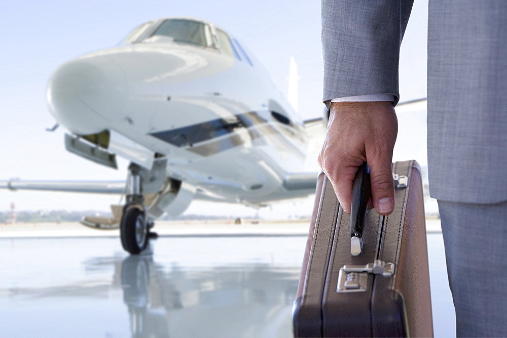 Close Up Of Businessman With Briefcase By Private Airplane