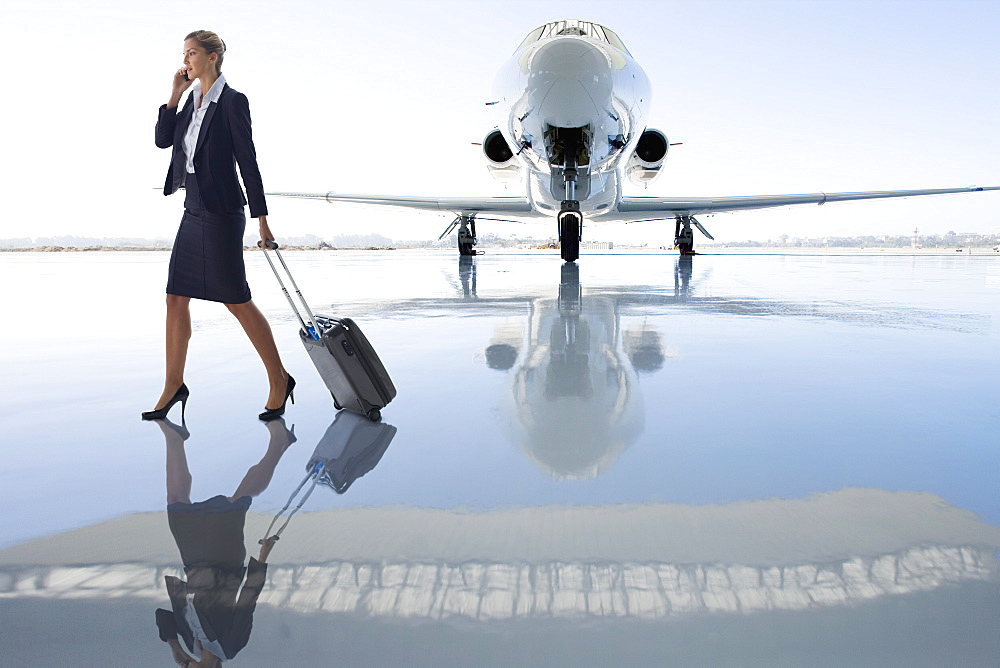 Businesswoman Using Mobile Phone By Private Airplane