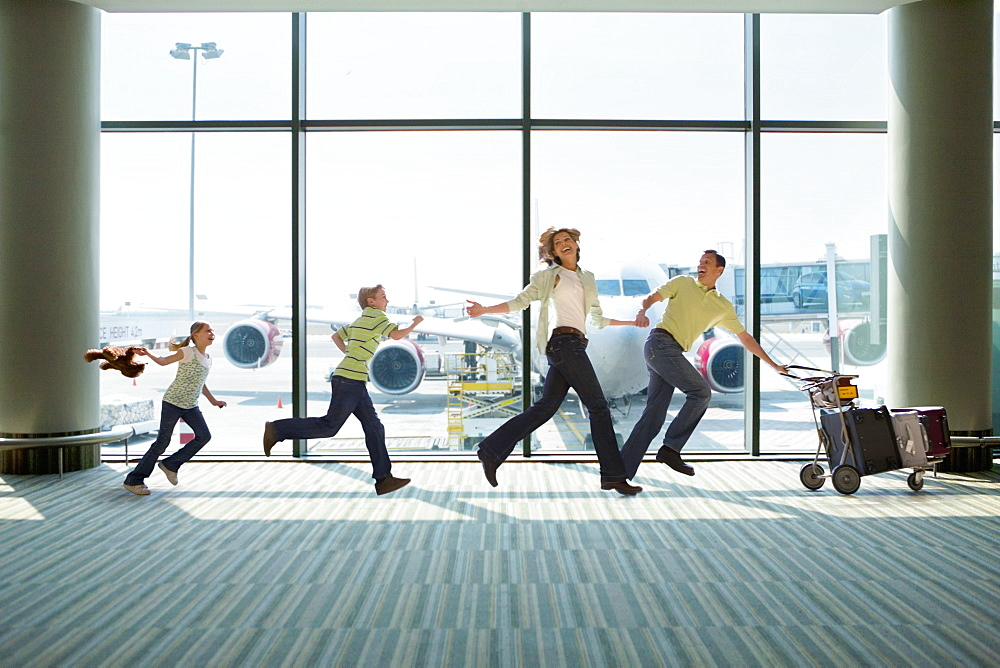 Family Running To Catch Flight In Airport Departure Lounge