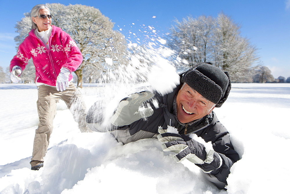 Romantic Mature Couple Having Snowball Fight In Countryside - 786-10283