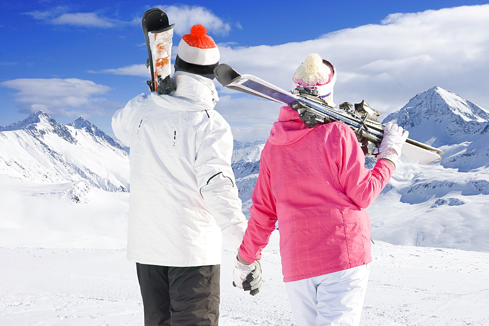 Rear View Of Couple Enjoying Winter Ski Holiday In Mountains - 786-10285